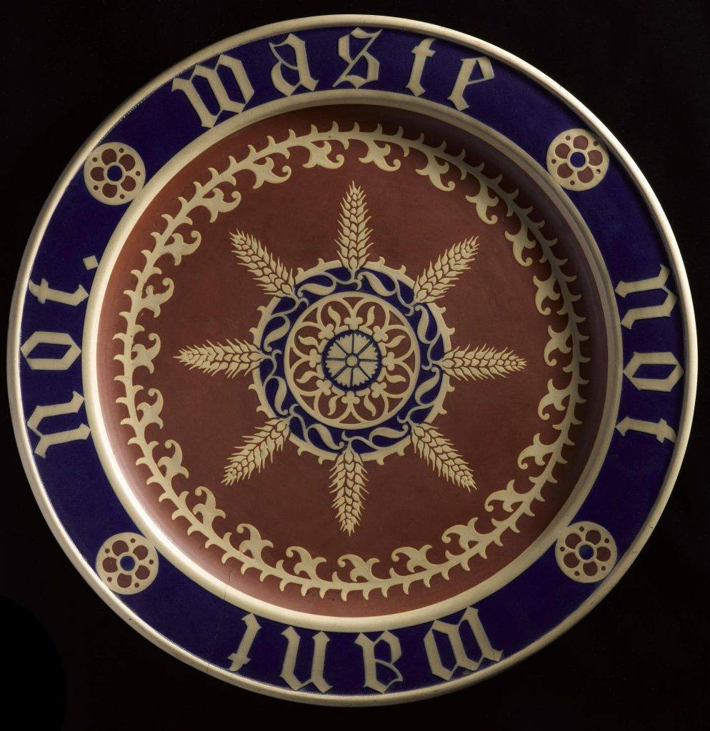 Deep Blue, Red and Gold plate decorated with leafy organic design. 'Waste Not Want Not' is painted in gold around the brim of the plate.