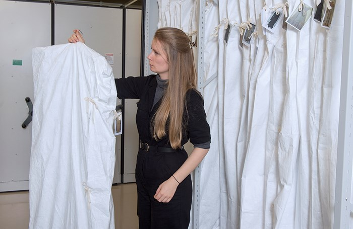 A collections technician next to a rail of hanging garments in white covers. There is a small picture of each garment tied to the outside of each garment to identify what is in each bag. She's holding up one of the hanging garments and looking at it.
