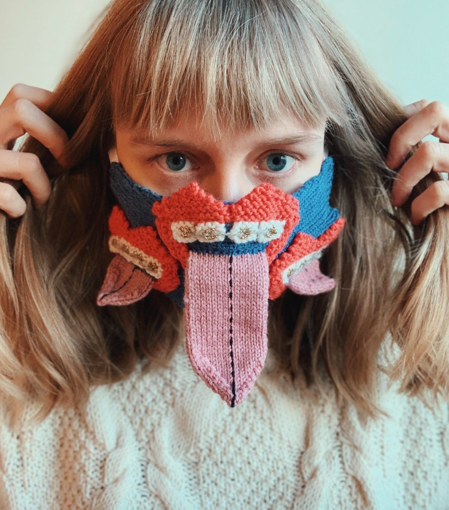The artist wearing the final design. A blue knitted mask with with three crocheted mouths on the front of the mask. The mouths are bold red with toothy grins. There are braces on the teeth, and. Long pink tongues are rolling out of each 'mouth'.