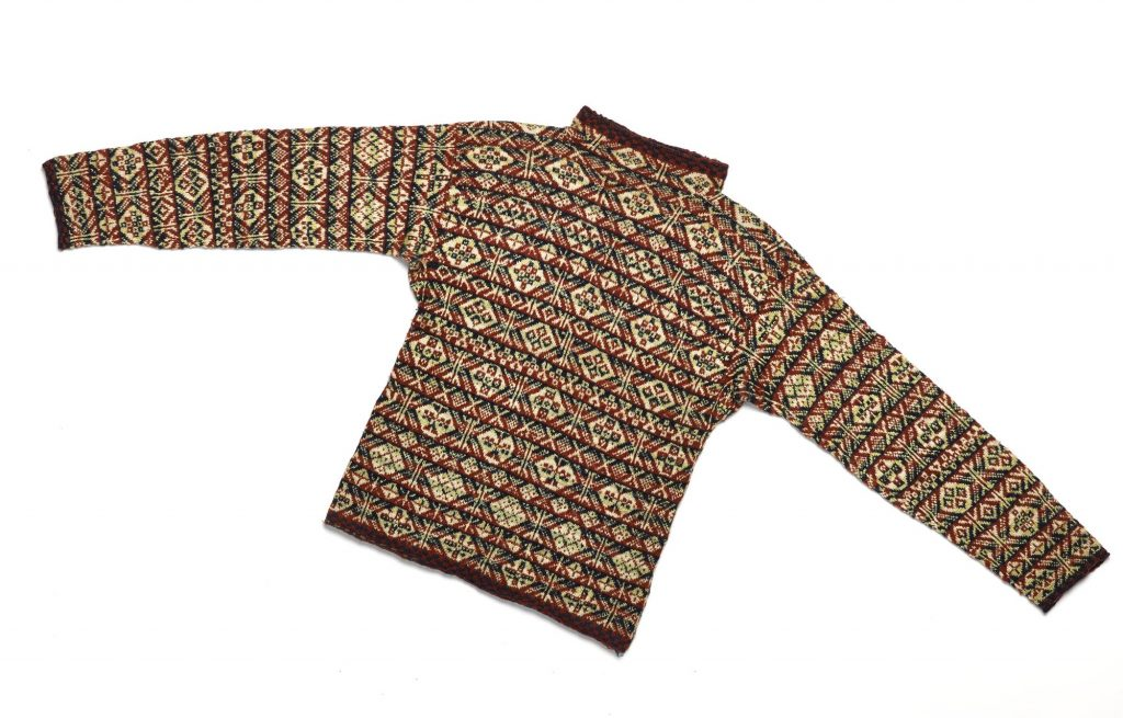 Jumper in Fair Isle pattern knitted wool, with a high round neck and long sleeves, and a chequered design in red and blue on the neck, hem and cuffs