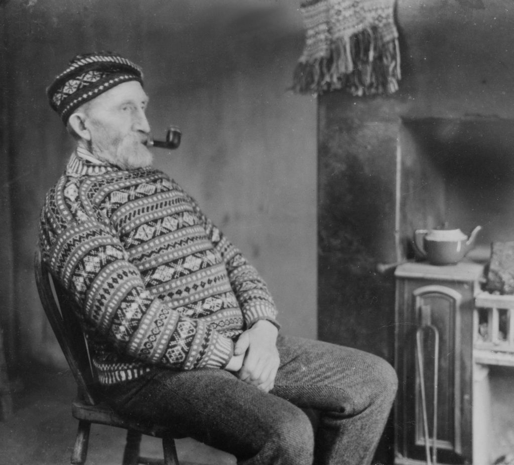 Black and white image of an older man with a white beard, smoking a pipe, sitting near a fireplace. He's wearing a cosy Fair Isle knit jumper with a matching bunnet made in the same pattern.