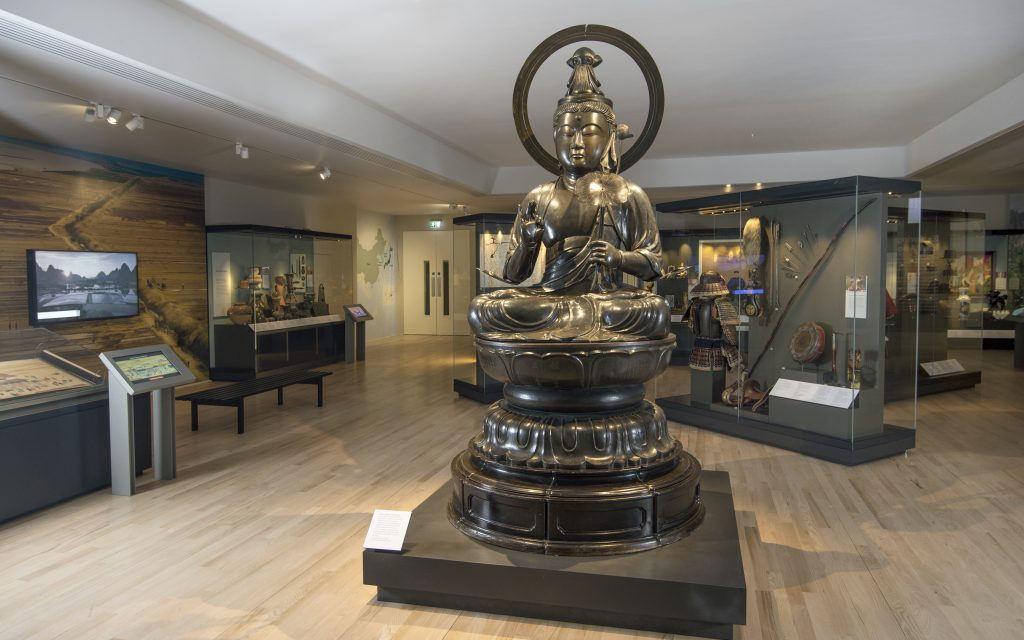 Photo of a gallery at the National Museum of Scotland showing a large Buddha statue among object cases.