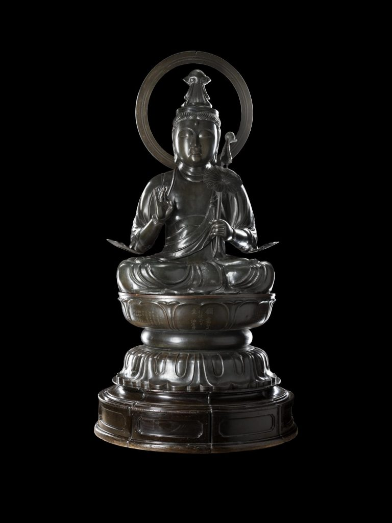 A large Buddha statue photographed against a black background.