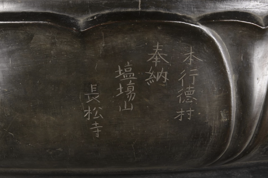 Close-up photo of the statue with Japanese characters inscribed on it.