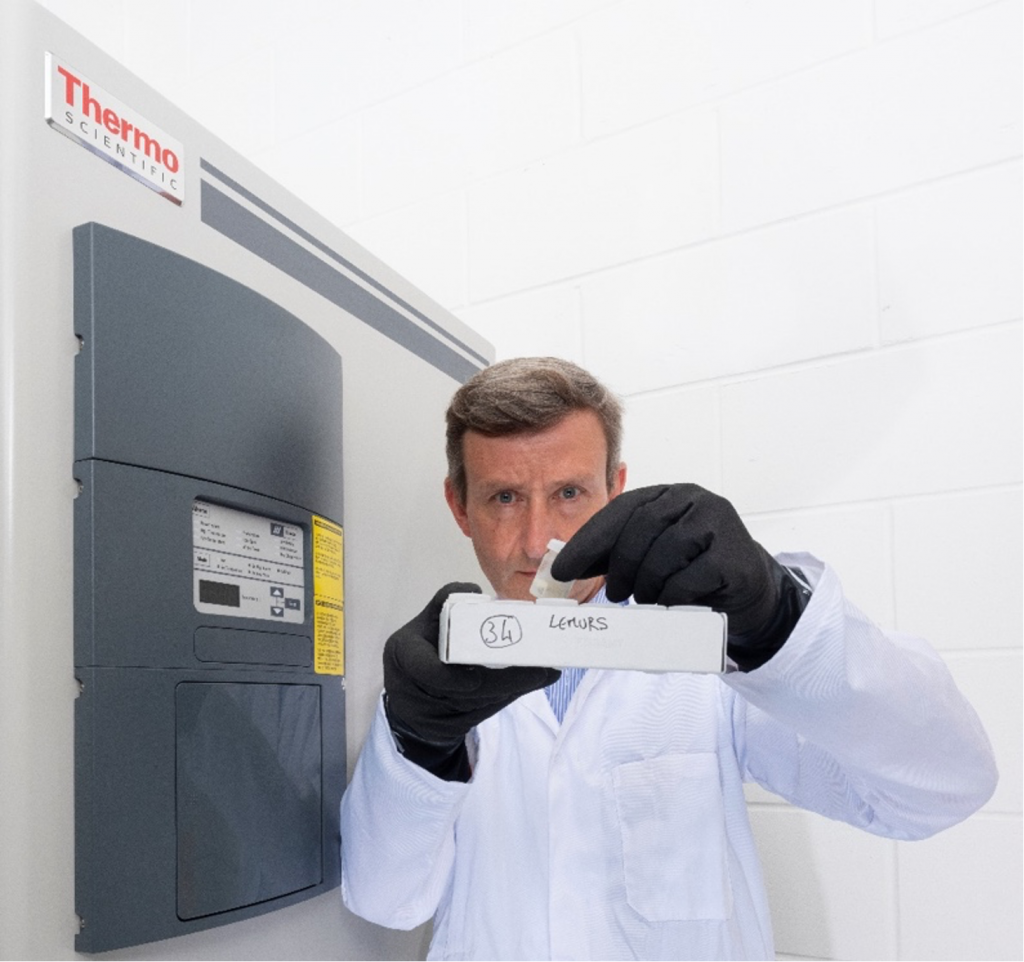 A man in front of an industrial freezer holding up a frozen tissue sample in a vial.