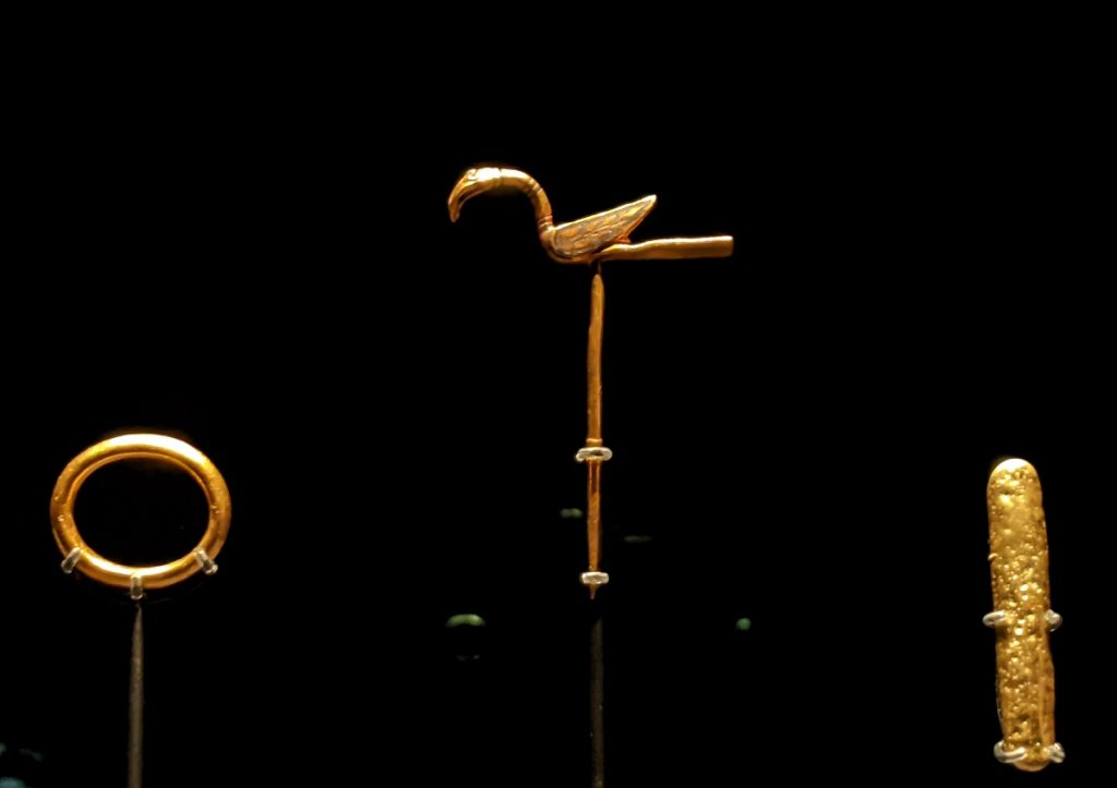 Three golden objects, a ring, bird-shaped pin, and finger-shaped ingot, suspended against a black background.