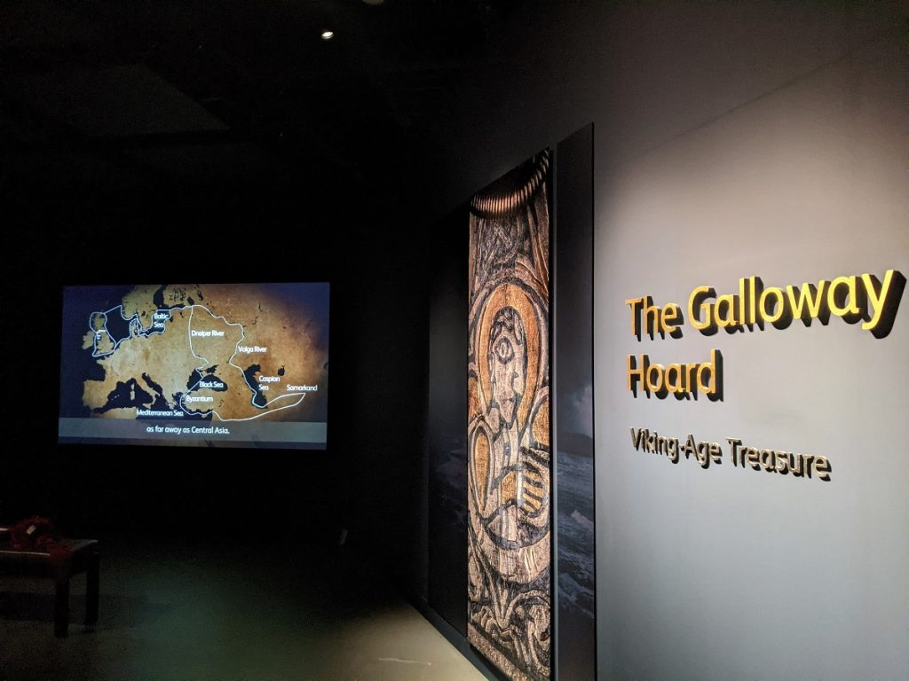 A screen on the left shows a map of Europe and Central Asia. Vertical panel in centre shows a metal engraving of a person, with 'The Galloway Hoard' written in gold letters on a grey wall.