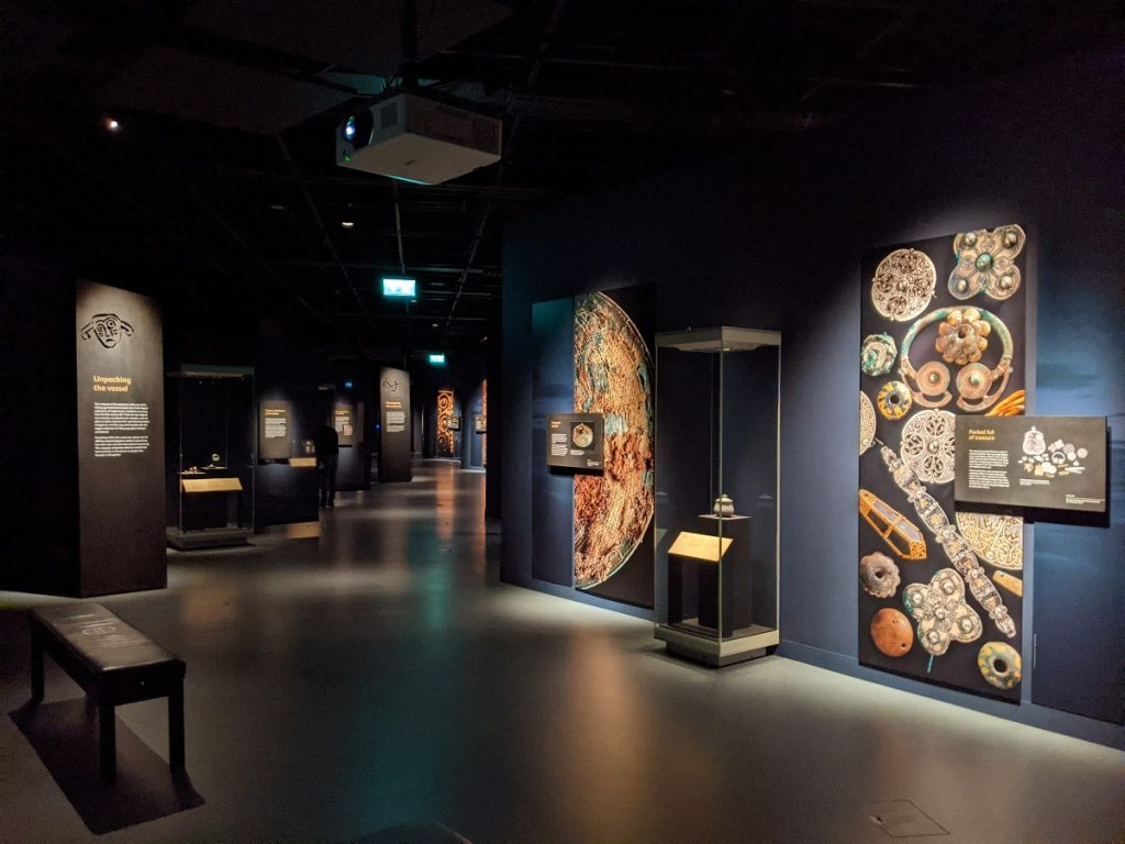An dimly-lit aisle curves and continues into the distance, flanked by glass cases and vertical panels showing objects from the Hoard.