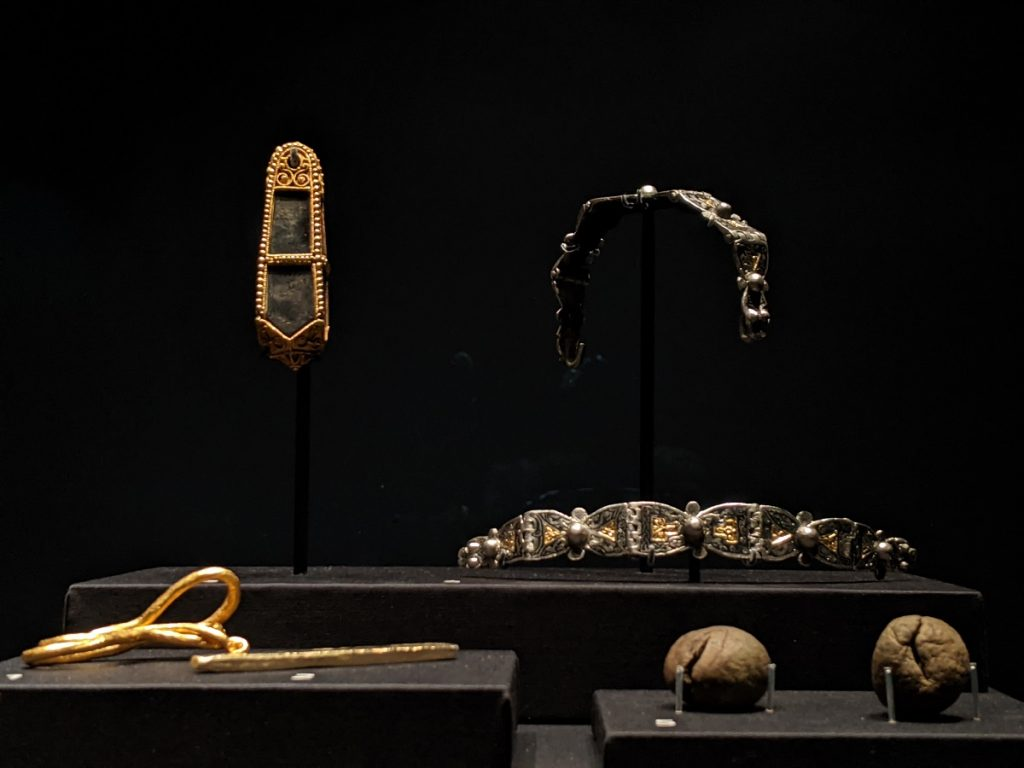 A cluster objects against a black background. Encased black stone at top left, two arm-bands at top right, two dirt-balls at bottom left, and two thin strips of gold at bottom left.