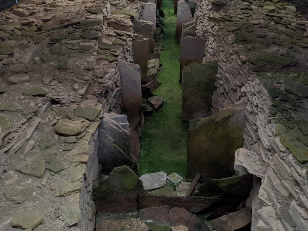 View from 45 degrees of the long central corridor and side cells. The floor of the corridor is vivid green against greyish-brown stones.
