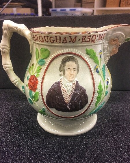 The jug from the side, highlighting the portrait of Brougham wearing a brown suit. Floral motifs flank him, with 'Brougham.esq:M.P' written above him.