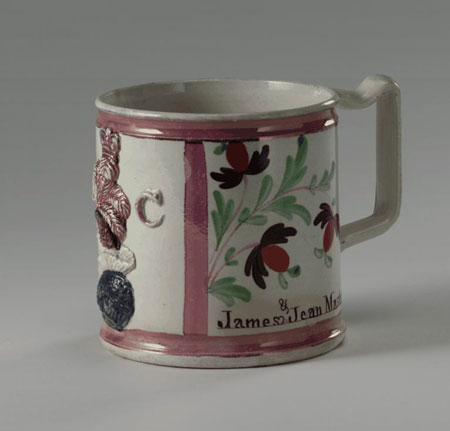 Short, stour mug with pink stripes framing panels featuring Caroline, fruits growing on vines, and the names 'James & Jean Masterton'.
