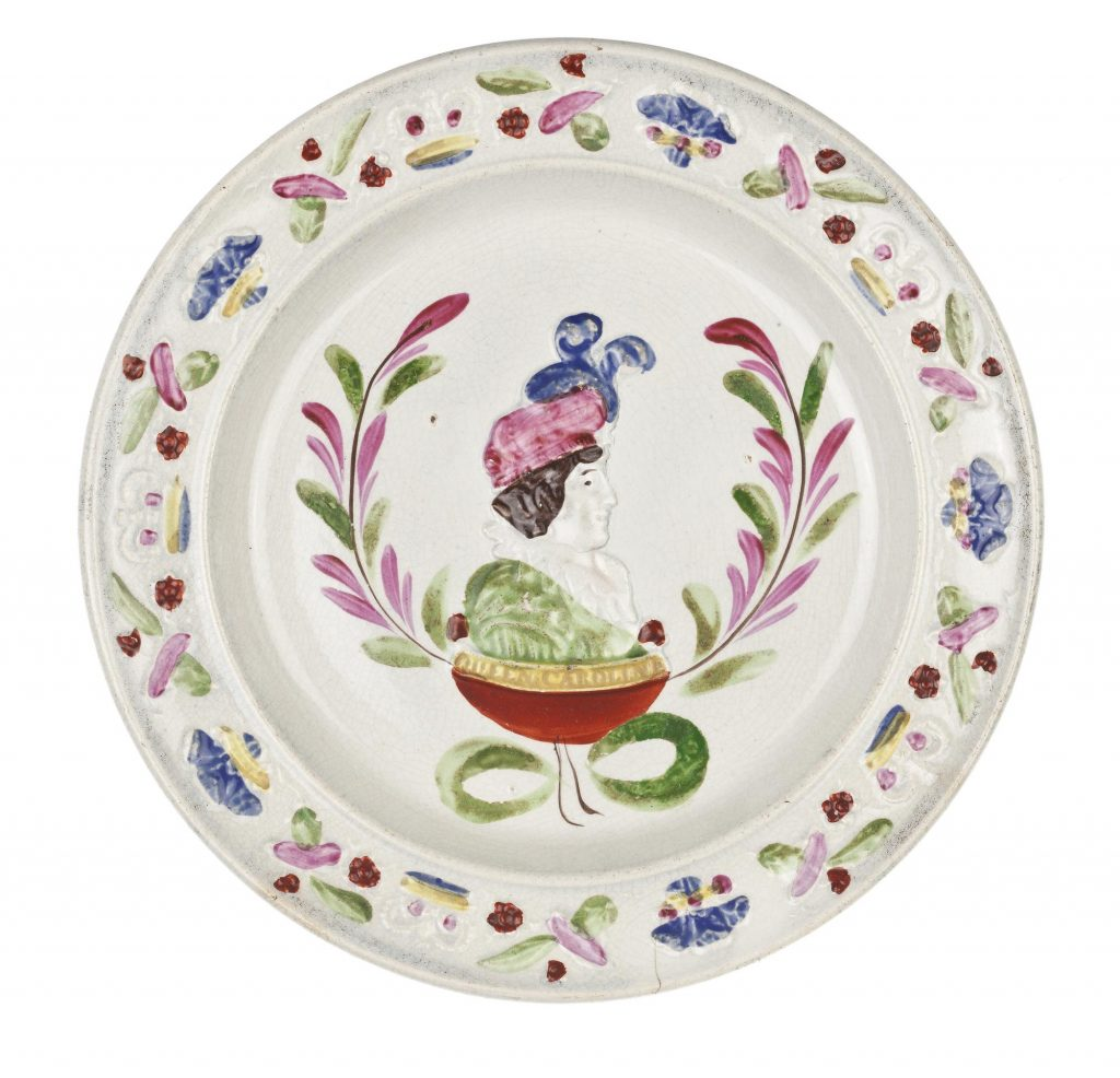 Off-white plate with Caroline, wearing a green dress and pink hat with blue feathers, in centre. Crowns and vegetables border the plate.
