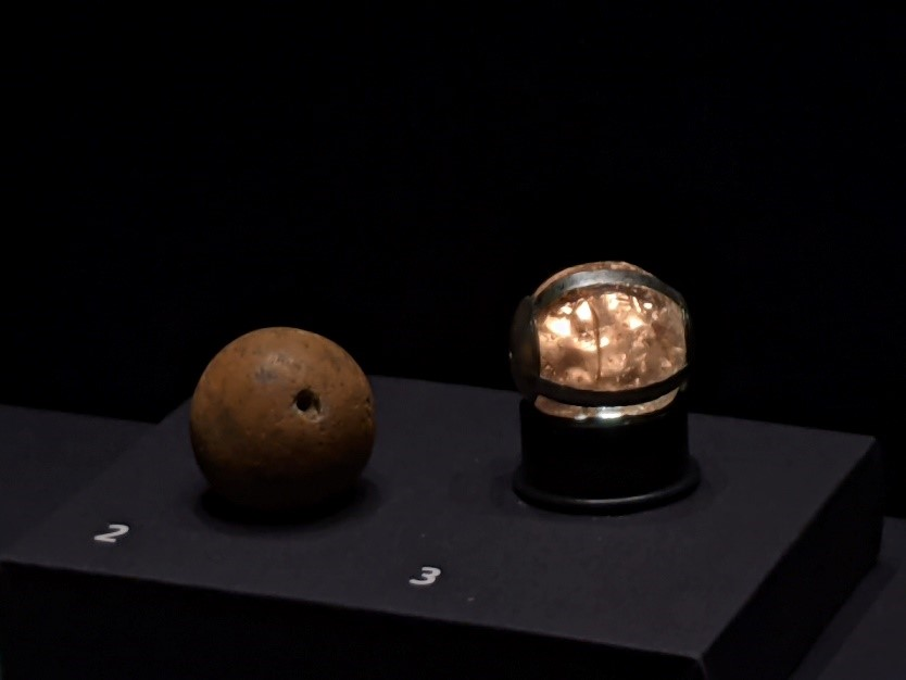 Side view of a brown rocky sphere on the left and a metal-encased sphere on the right which resembled translucent glass and seems to glow yellow from within.
