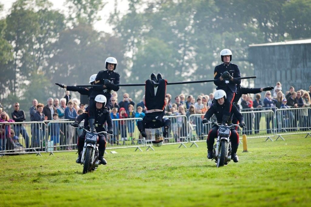 Two motorcycles each with two people on them ride through a field. A bar connects them and a person is hanging onto the bar.
