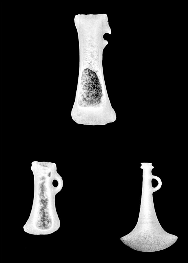 X-ray image of three axeheads. The axeheads appear in bright white with shading inside them against a black background.