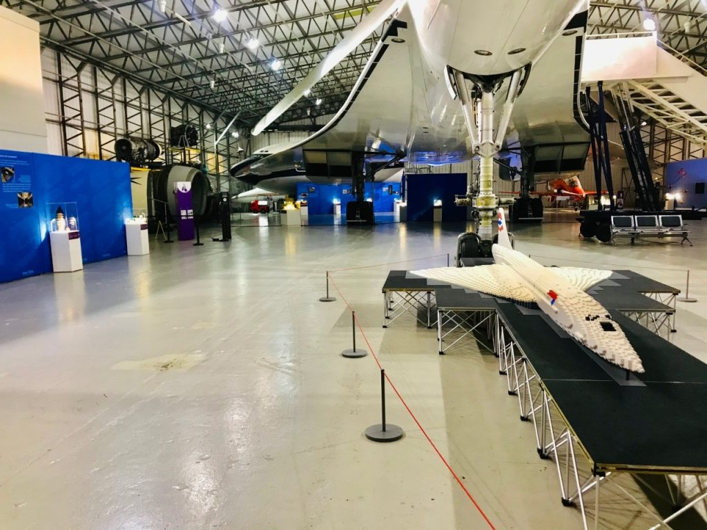 Floor of a large white airplane hangar. A real Concorde looms over a LEGO scale model of itself.