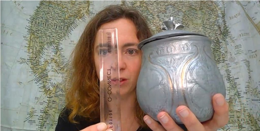 A woman with shoulder-length brown hair holds a glass tube in front of her face in one hand, and a replica silver  pear-shaped vessel in the other.