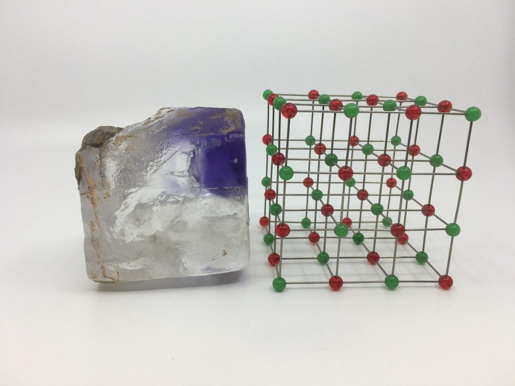 A roughly square chunk of grey and bright blue mineral sits on a white surface next to a lattice-like cube.