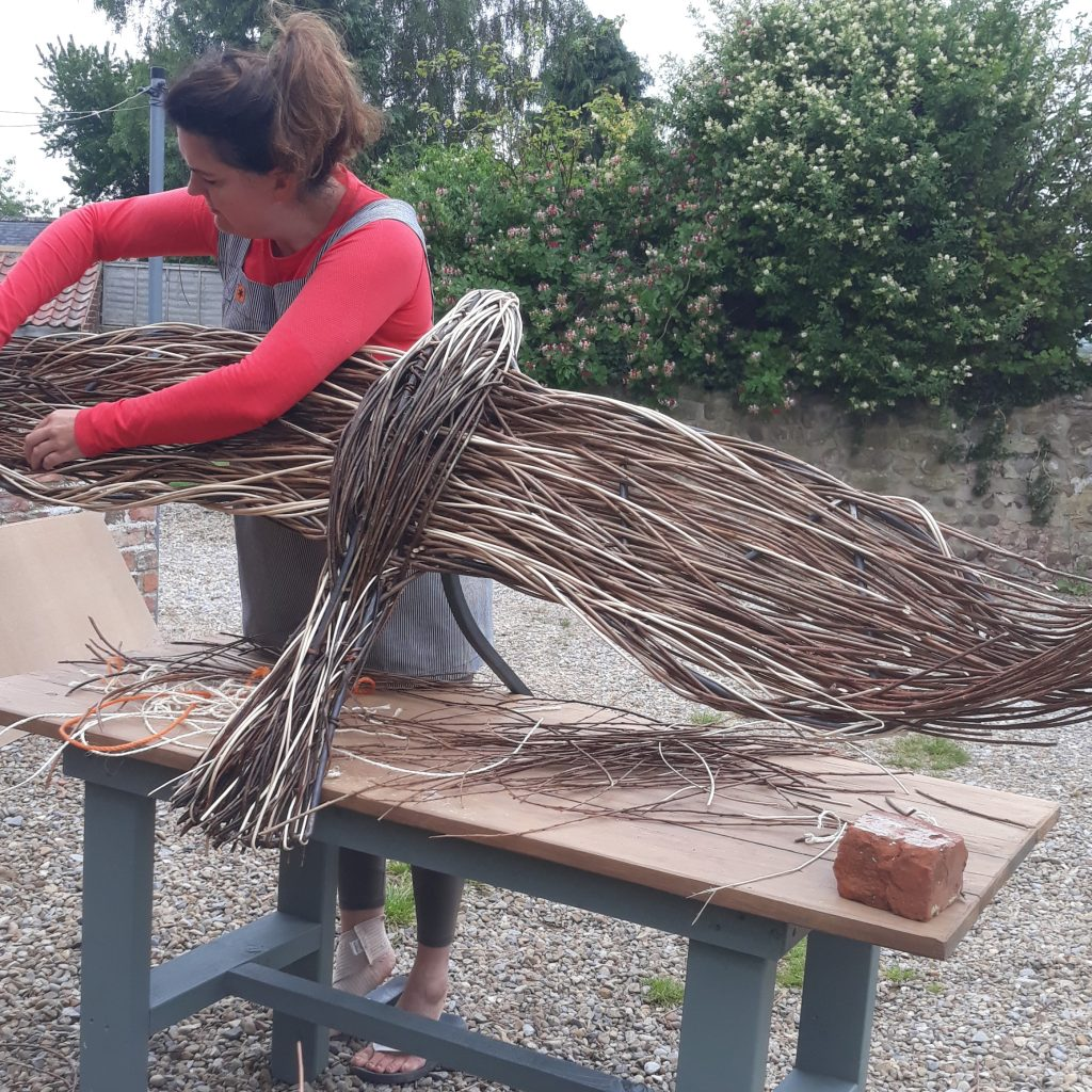 Colour photo of a woman standing behind a workbench and weaving a willow sculpture by hand.