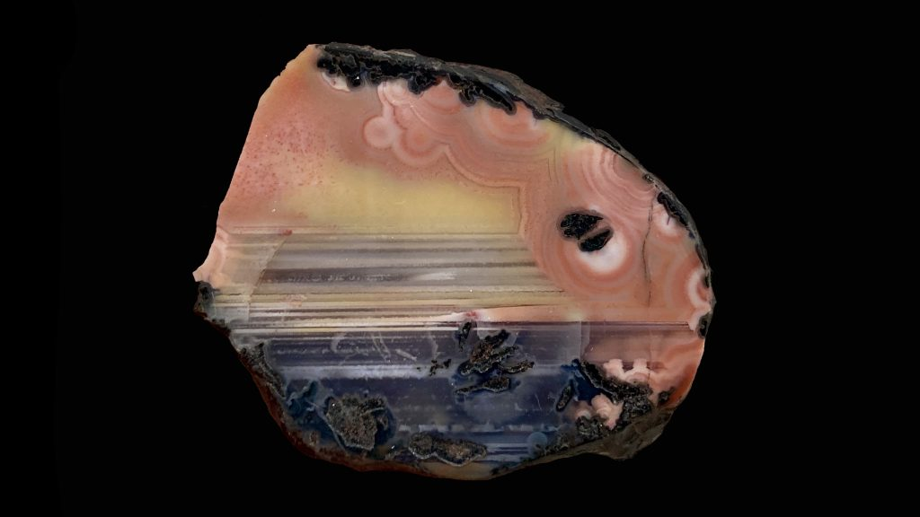 A peach and yellow and blue agate that resembles a sunset from a beach.