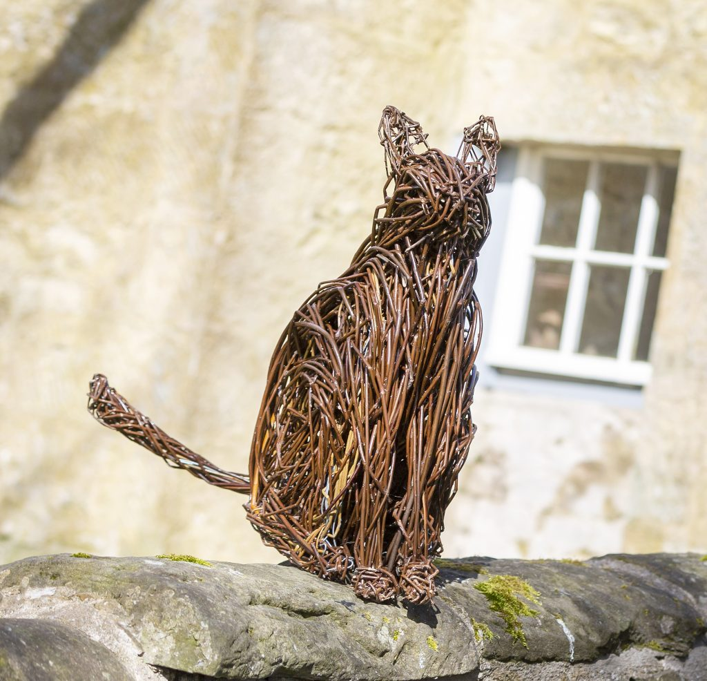 Colour photo of a cat willow sculpture sitting on a farm wall.